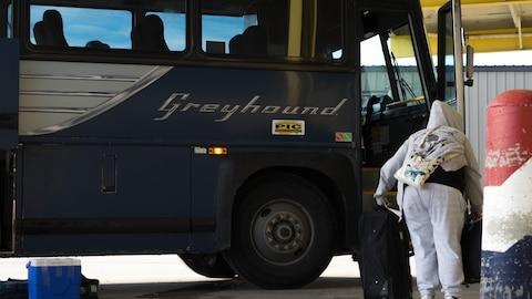 Une femme monte dans un autobus Greyhound.