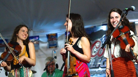 Trois jeunes femmes violonistes sur une scène.