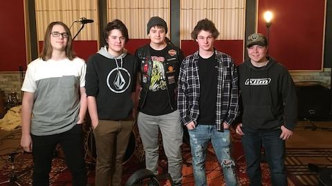Les cinq jeunes musiciens côte à côte en studio