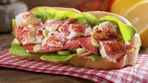 Un pain hot-dog rempli de chair de crabe, salade et crème juteuse, sur une serviette de table à carreaux.