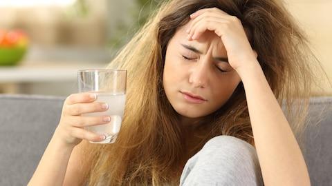 Une jeune femme, les yeux fermés, se tient la tête d'une main avec un verre d'eau dans l'autre.