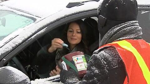 Une conductrice en train de mettre un billet de banque dans une boite tenue par un homme.