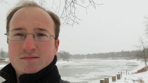 Un homme devant une rivière gelée.