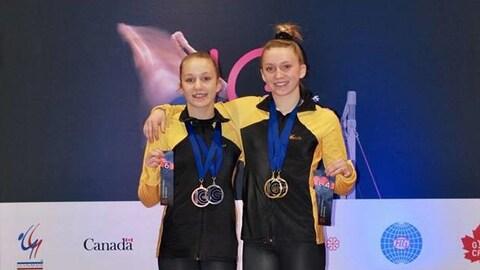 Deux jeunes femmes posent avec leurs médailles au cou.
