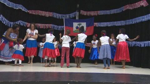 Un groupe de jeune en train de danser sur scène. Ils portent les couleur du drapeau haïtien.