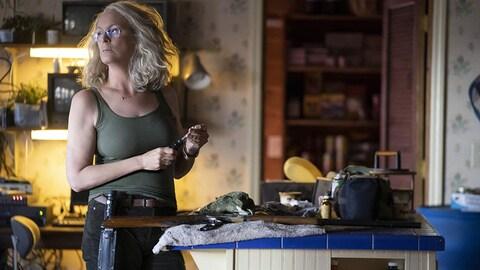 Jamie Lee Curtis tient un couteau et a posé un fusil sur une table dans la version 2018 du film d'horreur «Halloween».