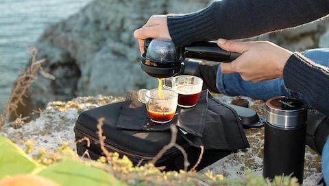 Un homme extrait un espresso grâce à un Handpresso.