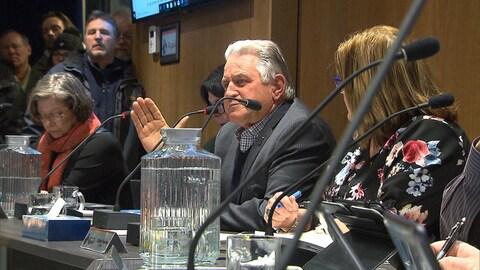 Assis à la table du conseil, le maire prend la parole.