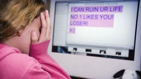 Une jeune fille couvre son visage de ses mains, devant elle se trouve un écran d'ordinateur où apparaissent des menaces et des insultes.