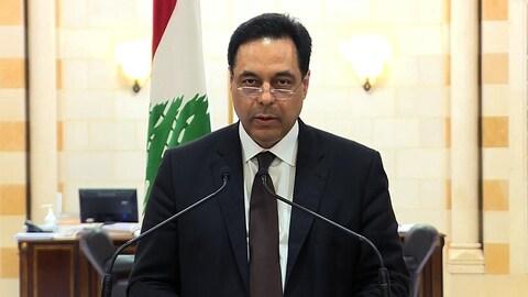 Hassan Diab prend la parole derrière un lutrin.