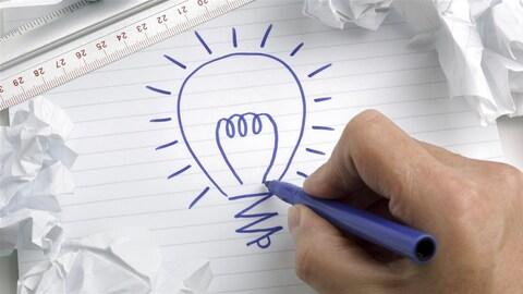 Un homme dessine une ampoule, symbole de l'idée.