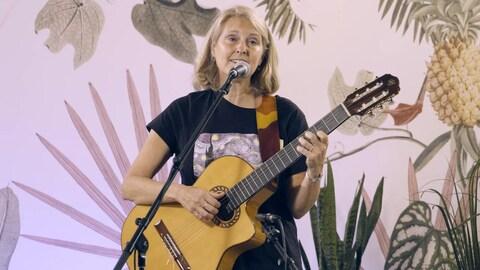 L'auteure-compositrice-interprète Hélène Perreault avec sa guitare derrière un micro.