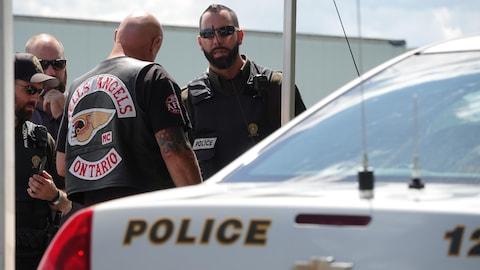 Un policier de la Sûreté du Québec discute avec un membre des Hells Angels.