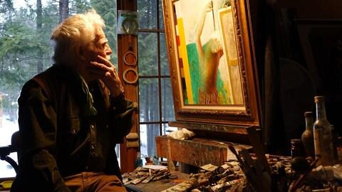 Henry Wanton Jones assis devant son chevalet regarde une peinture.