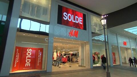 Un magasin H&M avec de grandes affiches sur lesquelles apparaît le mot « solde ».