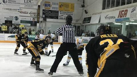 Des hockeyeurs des Bruins d'Estevan et les Hawks de Nipawin s'apprêtent à se lancer sur la rondelle samedi 14 avril 2018 dans un aréna en Saskatchewan
