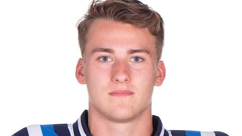 Un jeune homme portant un uniforme de hockey.