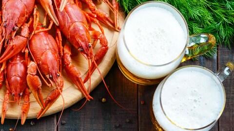 Homards dans une assiette et deux chopes de bière.