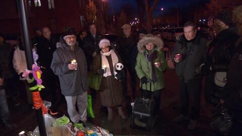 Des personnes rassemblées portant des bougies