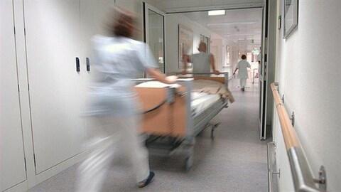 Des infirmiers transportent une civière dans le couloir d'un hôpital.