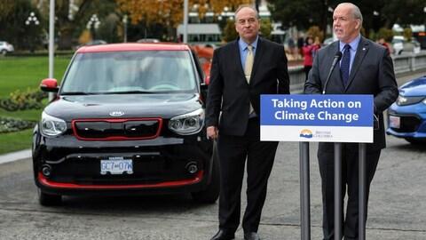 Deux politiciens devant des véhicules électriques.