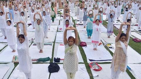 Des femmes indiennes pratiquent le yoga en tenue traditionnelle.