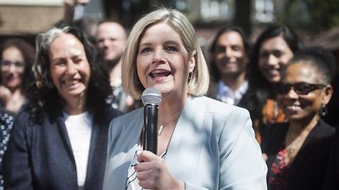 Une femme tient un micro et se tient devant d'autres femmes