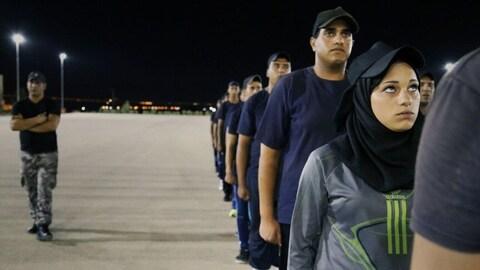 Des soldats sur un terrain d'entraînement au garde-à-vous. Une femme voilée au premier plan.