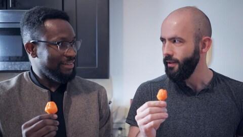 Une capture d'écran montrant un homme noir (Rachid) et un homme blanc (Andrew Rea) tenant chacun un petit piment fort orange entre leurs doigts.