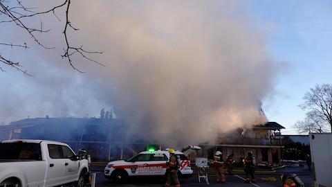 Plusieurs pompiers sont actifs devant l'hôtel Econo Lodge. Un panache de fumée s'échappe de l'établissement.