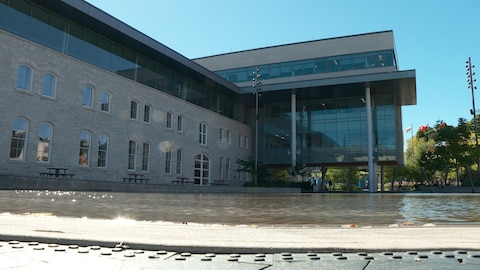 Grand bâtiment avec beaucoup de fenêtres vu en contre-plongée. On voit une étendue d'eau en face de l'édifice.