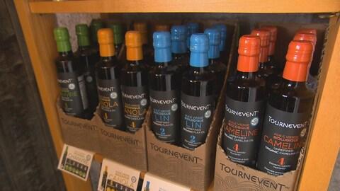 Des bouteilles d'huile Tournevent dans un présentoir.
