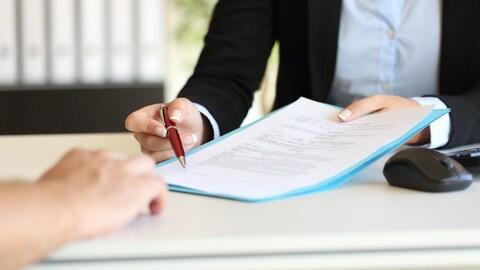 Des mains d'un employé tiennent des documents en indiquant avec un stylo l'endroit où une personne lui faisant face doit signer.