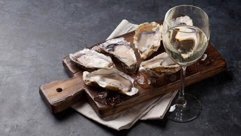 Un plateau avec des huîtres ouvertes et un verre de vin blanc.