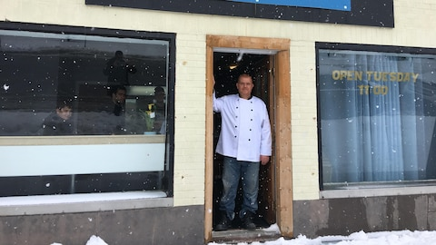 Un homme devant la façade d'un restaurant.