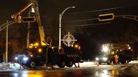 Des travailleurs d'Hydro-Québec avec leur camion.