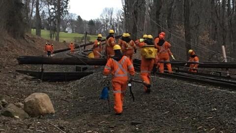 Des monteurs de lignes travaillent près d'un chemin de fer.