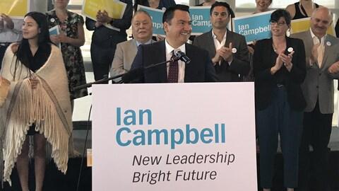 Ian Campbell devant un micro qui sourit. Il porte un complet bleu avec une cravate bourgogne.