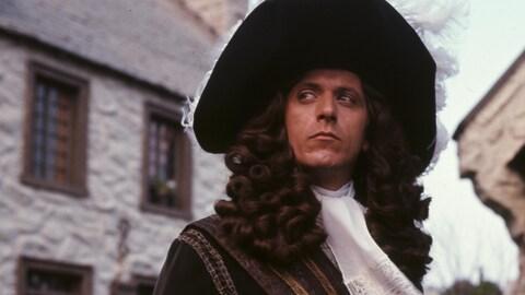 Devant des bâtiments en pierre, Albert Miller dans son rôle de Pierre Le Moyne d'Iberville.