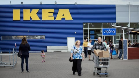 Plusieurs personnes sortent d'un magasin Ikea avec des paquets.
