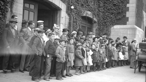 Photo noir et blanc du premier groupe de Madelinots qui prennent la direction de l'Abitibi en 1941. Ils sont réunis à la gare de Québec, les hommes et les femmes derrière, les enfants devant.