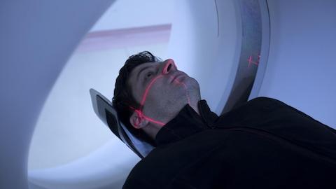 Un homme passe un examen d'imagerie par résonance magnétique.