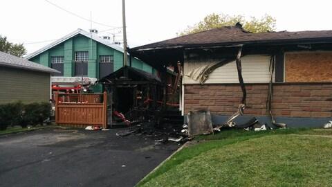 Photographie d'une maison unifamiliale endommagée par les flammes. Le toit de la demeure s'est en partie effondré. Un cabanon situé sur le côté de la maison est complètement calciné.