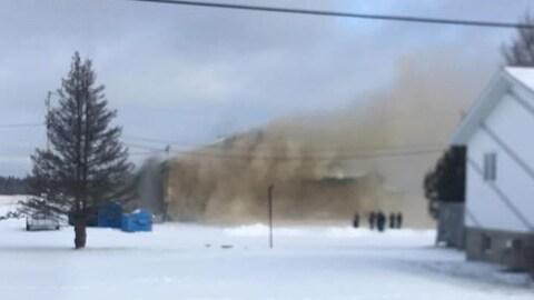Un épais panache de fumée s'échappe d'un bâtiment de ferme.