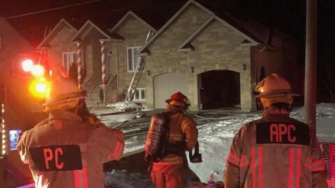 Des pompiers devant une résidence.