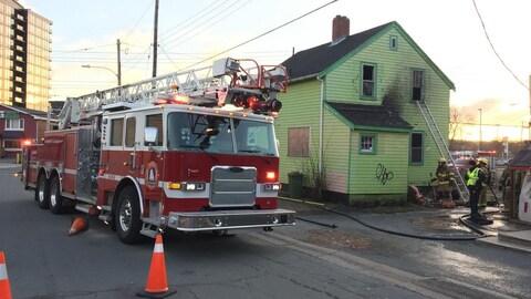Des pompiers arrosent le bâtiment vert abritant Greenhouse Wellness, le 15 novembre 2018 à Halifax.