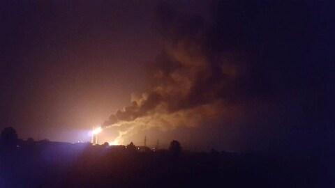Un grand incendie et des colonnes de fumée au loin dans la nuit.