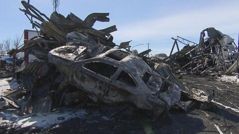 Des morceaux de métal et une carcasse de voiture carbonisés