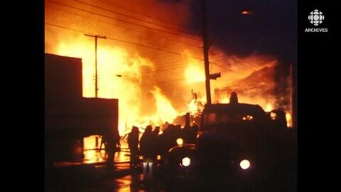 Des volontaires et des curieux s'attroupent autour d'un pâté de maison ravagé par le feu.