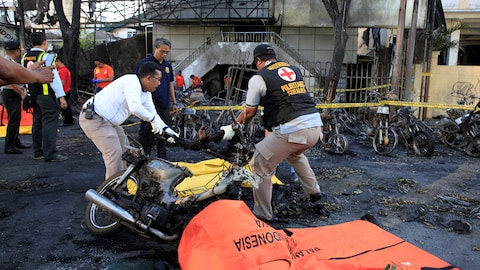 Des secouristes déplacent le corps d'une victime des attentats perpétrés contre plusieurs églises indonésiennes.